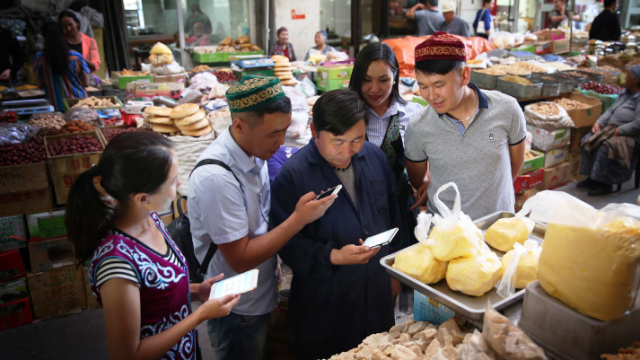 Merchants use mobile phones in marketplace