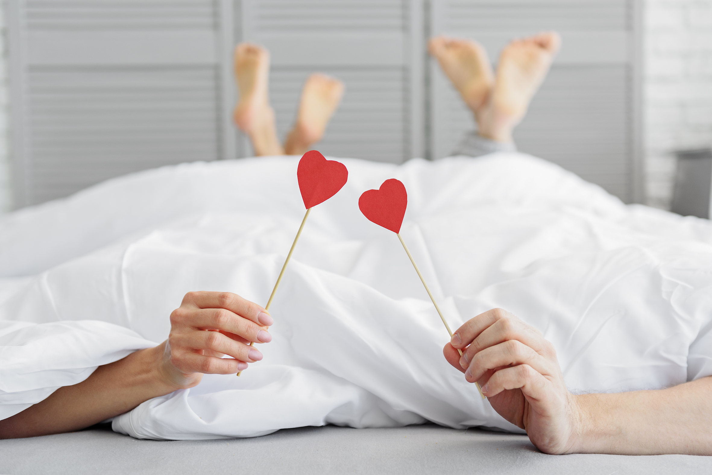 couple holding hearts in bed